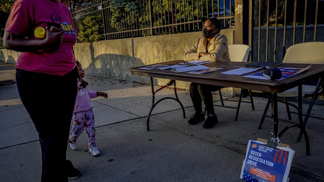 "A woman and child walk past Laurae Caruth, right, volunteer with Christian Cultural Center (CCC) Social Justice Initiative's voter registration drive, as she sits at a table outside the gates of the Brooklyn mega-church where unregistered voters can get registered, Friday Sept. 18, 2020, in New York.  ""I'm out here volunteering because of how important it is to exercise the right to vote,"" said Caruth. In recent election cycles, Black congregations nation-wide host ""souls to the polls,"" a get-out-the-vote campaign designed to counteract voter suppression, but will look different in 2020 due to the coronavirus pandemic."