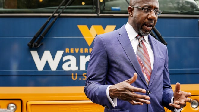 """Democratic candidate for Senate Raphael G. Warnock speaks to a crowd during a """"Get Out the Early Vote"""" event at the SluttyVegan ATL restaurant on Tuesday, Oct. 27, 2020, in Jonesboro, Ga."""