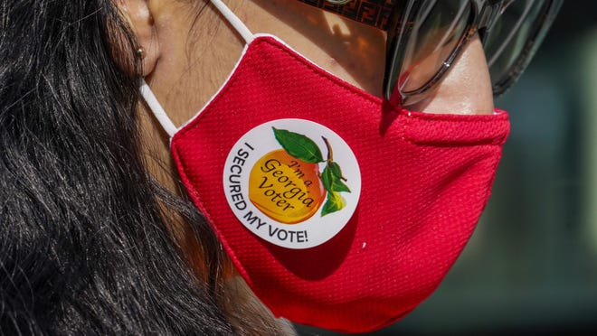 """A person wears a """"I'm a Georgia Voter"""" sticker after voting on Election Day in Atlanta on Tuesday, Nov. 3, 2020."""