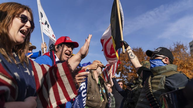 Trump supporters, at left, demonstrating the election results are confronted by counter protesters at the State Capitol in Lansing, Mich., Saturday, Nov. 7, 2020.  Democrat Joe Biden defeated President Donald Trump to become the 46th president of the United States on Saturday, positioning himself to lead a nation gripped by the historic pandemic and a confluence of economic and social turmoil.