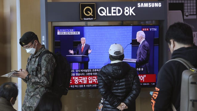 "A TV screen shows a live broadcast of U.S. President Donald Trump, left, and Democratic presidential candidate former Vice President Joe Biden during the final presidential debate, at the Seoul Railway Station in Seoul, South Korea, Friday, Oct. 23, 2020. The Korean letters read: ""U.S. presidential election TV debate."""