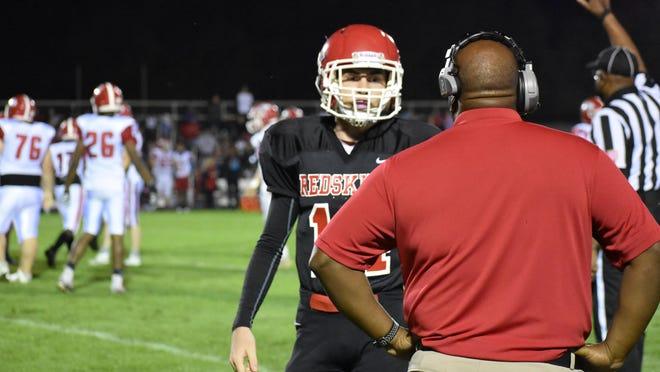 Bryan County quarterback Sean Kelly Hill gets a play call from head coach Cherard Freeman on Friday night against ECI in Pembroke.