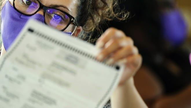 A election worker counts ballots at State Farm Arena on Thursday, Nov. 5, 2020, in Atlanta.