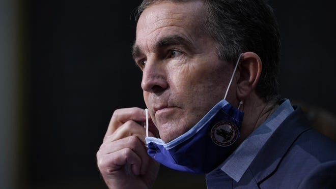 Virginia Gov. Ralph Northam removes his mask to answer a question during a COVID-19 briefing at the Capitol in Richmond, Va.