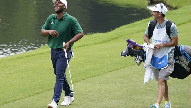 Chris Rice (right), the caddie for Harold Varner III, won the annual Players Championship caddie competition on Wednesday with a shot 14 inches from the hole at No. 17.