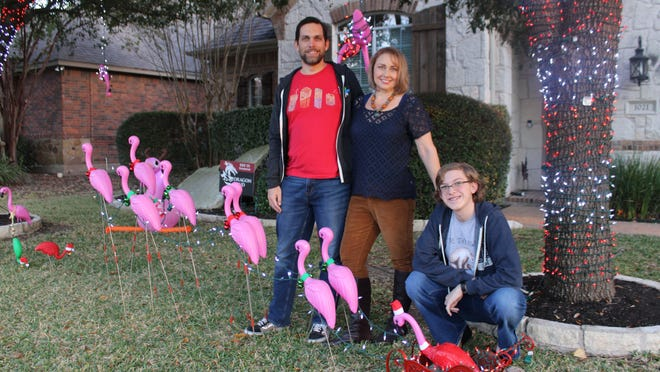 John Welsh, his wife Kristen and daughter Ess have created a flamingo Santa Claus being pulled by eight flamingo reindeer on their front lawn on Hidden Glen Drive.