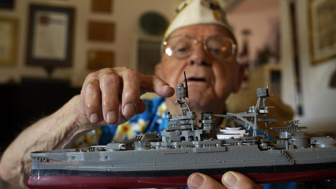 Mickey Ganitch holds up a model of the USS Pennsylvania and points to where he served as a lookout during the 1941 attack on Pearl Harbor, in the living room of his home in San Leandro, Calif., on Nov. 20, 2020.