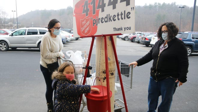 Shannon and Liz Schmitt, mother and daughter, guided Liz's daughter Peyton, 5, to drop money in the Salvation Army kettle, which is afamily tradition.