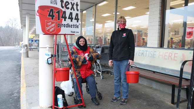 Captain Kelly Ross of the Port Jervis Salvation Army, right, picks up money collected by bell ringer Robin Colwell. Ross has been busy fielding requests for assistance.