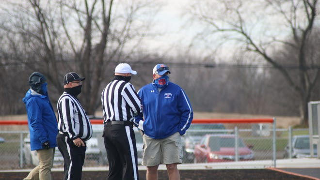 Lenawee Christian head coach Bill Wilharms, center, chats with officials before the Cougars' Division 1 8-man regional final game at Morrice High School on Saturday, November 14.