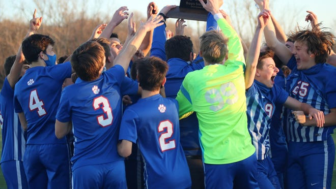 The Lenawee Christian boys soccer team celebrates with their trophy after winning the Division 4 state championship match 2-1 over Grandville Calvin Christian on Nov. 7, 2020 at Novi High School.