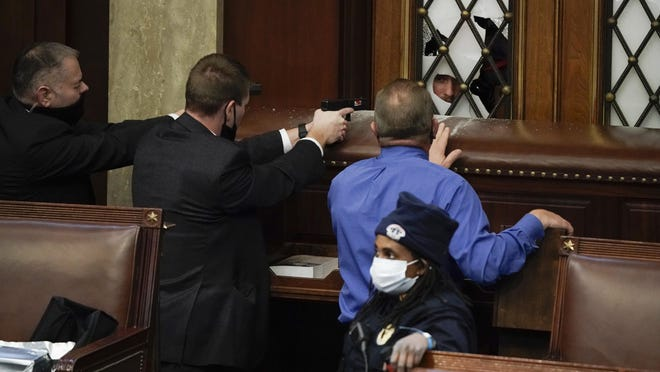 Police with guns drawn watch as protesters try to break into the House Chamber at the U.S. Capitol on Wednesday, Jan. 6, 2021, in Washington.