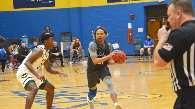 Lake Superior State senior guard Malek Adams handles the ball during a GLIAC game against Wayne State Saturday at the Bud Cooper Gym. The Lakers won 75-64 Saturday to split the two-game series.