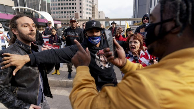 Trump supporter Charles Littleton, center, helps separate a fellow Trump supporter, left, from Biden supporter Angelo Austin, right, as they argue Thursday outside the central counting board at the TCF Center in Detroit.