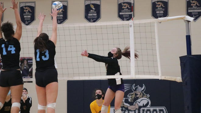 Blissfield senior Cendell Burgermeister (1) tips a ball over a block attempt by Lansing Catholic's Melissa Beachnau (14) and Alivia Castle (13) during their Division 2 regional semifinal on Tuesday at Lake Odessa Lakewood High School.