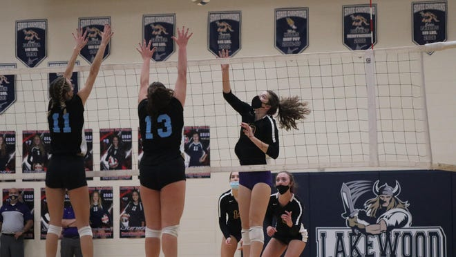 Blissfield sophomore Sarah Bettis (10) tips the ball over a block attempt by Lansing Catholic's Nikki Hufnagel (11) and Alivia Castle (13) during the second set of their Division 2 regional semifinal at Lake Odessa Lakewood Tuesday night.
