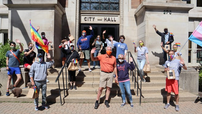 A group from Out on the Lakeshore, Holland LGBT community center, meets with Holland Mayor Nathan Bocks outside City Hall. The group spent a weekend delivering Pride flags to local businesses that have supported OOTL and Holland Pride in the past.