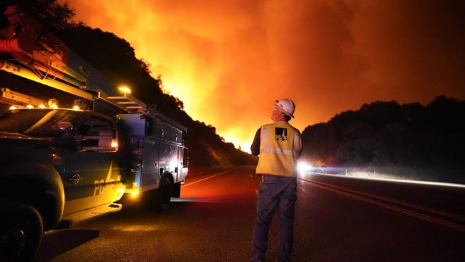 A Pacific Gas and Electric worker looks up at the advancing Creek Fire along Highway 168 Tuesday, Sept. 8, 2020, near Alder Springs, Calif.