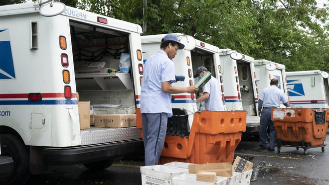 """In this July 31 file photo, letter carriers load mail trucks for deliveries at a U.S. Postal Service facility in McLean, Va. A U.S. judge on Thursday, Sept. 17, 2020, blocked controversial Postal Service changes that have slowed mail nationwide. The judge called them """"a politically motivated attack on the efficiency of the Postal Service"""" before the November election."""