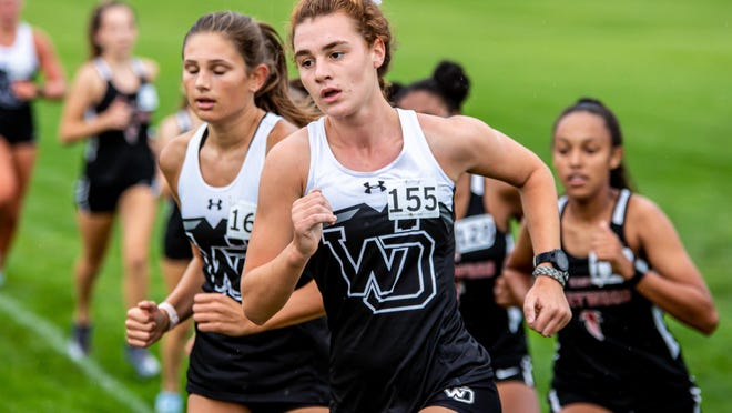 Kaia Denhof (center) has helped the West Ottawa cross country team win conference and regional titles.