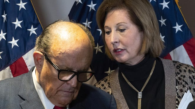 Former Mayor of New York Rudy Giuliani, left, listens to Sidney Powell, both lawyers for President Donald Trump, during a news conference at the Republican National Committee headquarters, Thursday Nov. 19, 2020, in Washington.