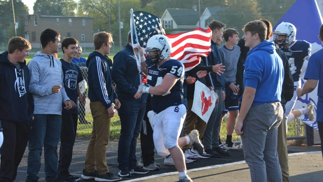Sault High's Cole Biron carries the American Flag as he leads the Blue Devils onto the field for the home opening football game of 2019. The 2020 Blue Devils have started official practice, getting ready for this year's season opener at St. Ignace on Aug. 28.