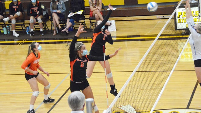 Rudyard's Sara Beelen (5) and Laine Grenfell (8) lead an attack during a regional final volleyball match against Inland Lakes Thursday night in Pellston.