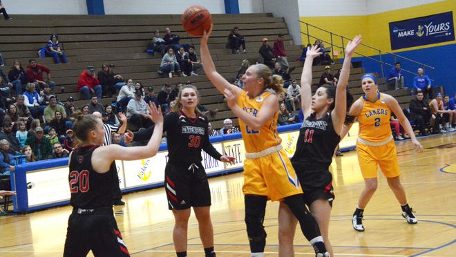 Lake Superior State's Sadie DeWildt (22) puts up a shot over Davenport's Taylor Opolka (20) during a GLIAC women's basketball game last season at the Bud Cooper Gym. The GLIAC announced its women's and men's basketball schedules Thursday. LSSU opens GLIAC play on Jan. 7.