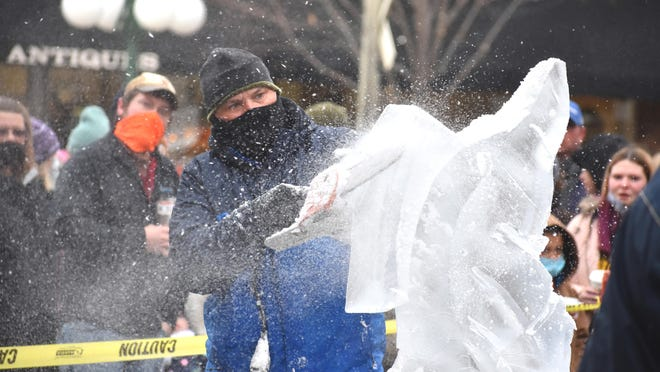 Jim Hauser, an ice sculptor with Napoleon, Ohio-based Ice Creations, sends some ice flying as he carves into his design of a fish jumping out of water Saturday during the dueling ice carving competition of the Ice Sculpture Festival in downtown Tecumseh.