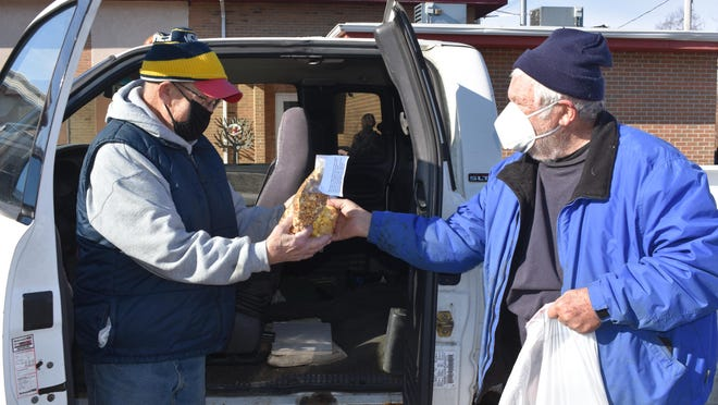 Larry Horn of Adrian, left, receives a bag of gourmet popcorn from Jerry Underfer, a longtime Hudson and Round Lake resident, Friday afternoon in the parking lot of the Adrian Senior Center, 327 Erie St. Underfer delivered the bags of popcorn to the senior center and its home-delivered meal drivers as a sign of appreciation for the volunteer work they do each day, especially during the past year amid the COVID-19 pandemic.