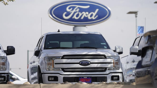 A row of 2020 sports-utility vehicles pickup trucks sits at a Ford dealership Sunday, Oct. 11, 2020, in Denver.