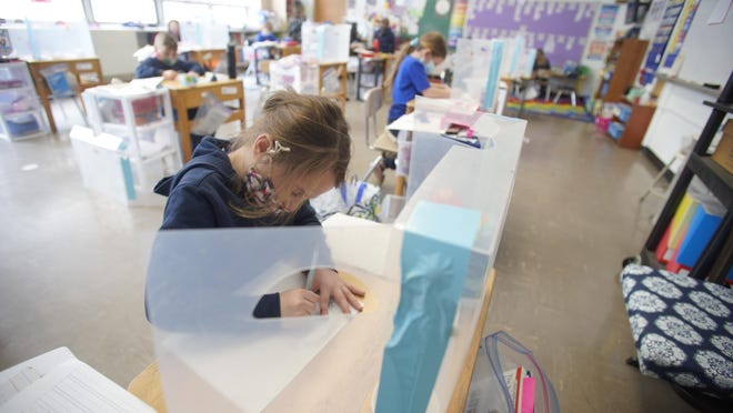 Anna Artist, 6, works on her classwork Thursday as St. Mary's School, a Catholic school in Lee, Mass., celebrates 100 days of no COVID-19 cases since all in-person school began in September.