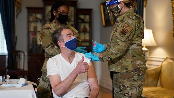 Virginia Gov. Ralph Northam gives a thumbs-up after receiving his COVID-19 vaccination from Lt. Col. Kris Clark, of the Virginia Air National Guard, at the Governor's Mansion in Richmond on Monday. Northam got a shot of the single-dose Johnson & Johnson vaccine.