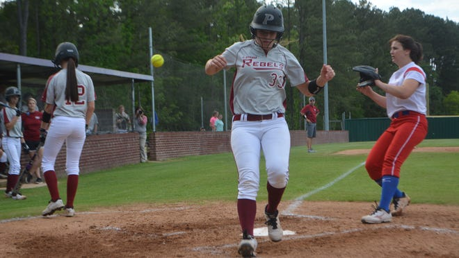 Pineville's Rebecca Martin (33, center) crosses home plate against Haughton Tuesday.