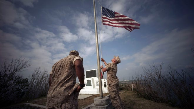 U.S. Marines hoist the U.S. flag on Saturday, March 21, 2015, on the summit of Mt. Suribachi, near the site of a ceremony commemorating the 70th anniversary of the Battle of Iwo Jima.