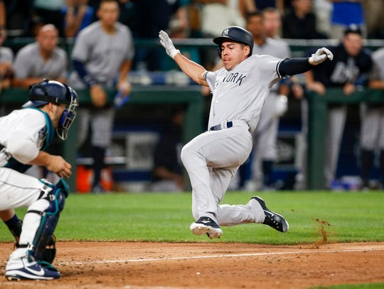 Yankees Jacoby Ellsbury slides home to score a run