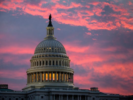 In this Thursday, Nov. 30, 2017, file photo, the sky over The Capitol is lit up at dawn as Senate Republicans work to pass their sweeping tax bill. (AP Photo/J. Scott Applewhite)