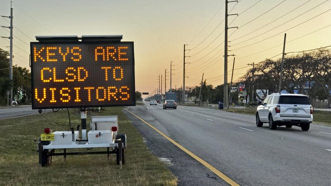 Cars pass an electronic messaging board on the Florida Keys Overseas Highway, Wednesday, March 25, 2020, in Key Largo, Fla. The coronavirus crisis has spurred Florida Keys officials to shut down the subtropical island chain to visitors until further notice. As far as the rest of Florida, Gov. Ron DeSantis last week mandated motorists from 'hotspot' states to isolate for 14 days upon entry to Florida or for the duration of their visit.