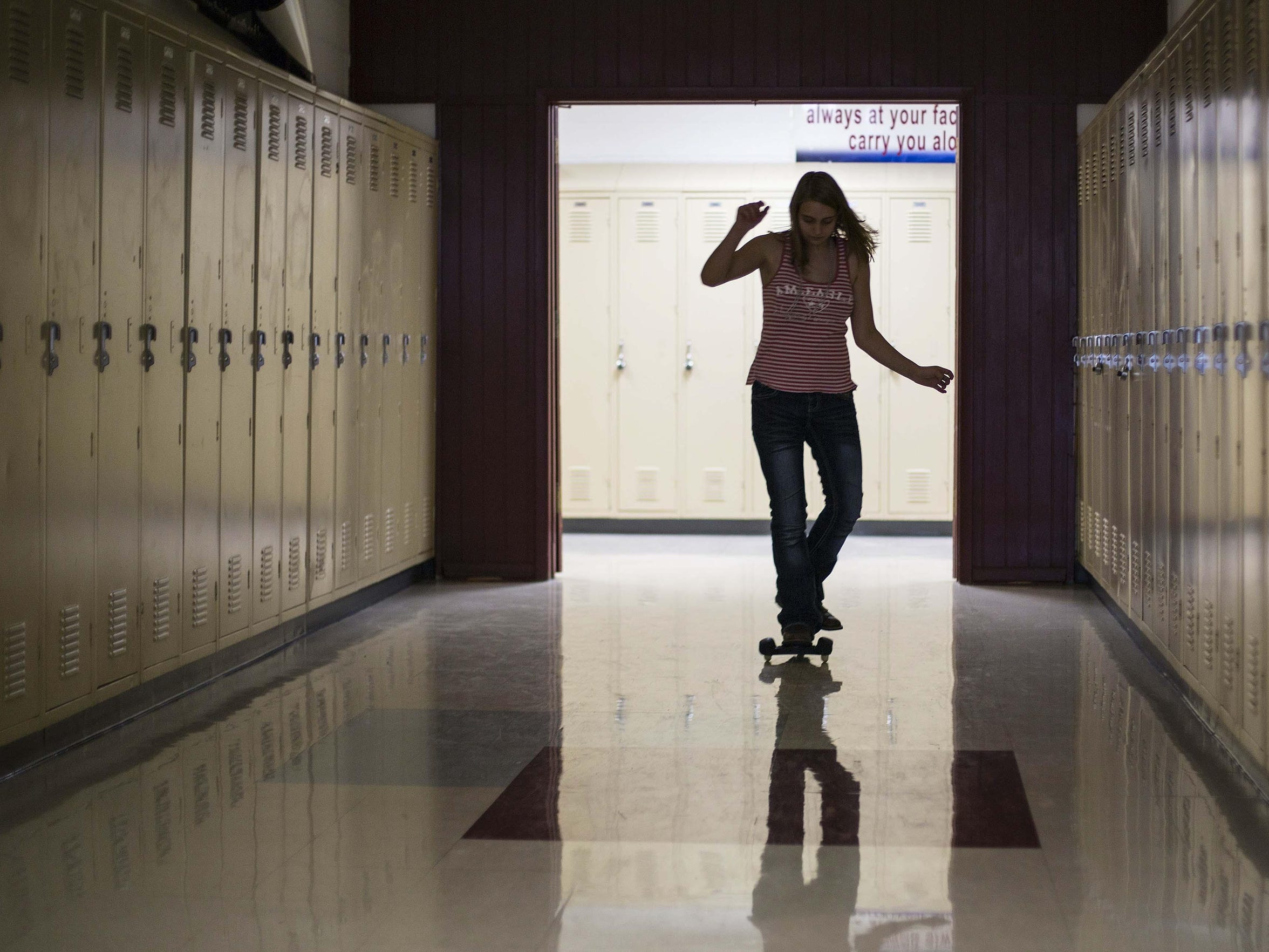 Tenth-grader Elizabeth Bell skates through a vacant hallway during the last minutes of the last day of class Friday May 29, 2015, at Corwith in the Corwith-Wesley school district.