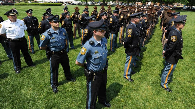 Police stand at attention Wednesday at Legislative Hall during a Fraternal Order of Police memorial for officers wounded or killed in the line of duty. Similar tributes were held at the headquarters of Delaware State Police and New Castle County Police on Wednesday.