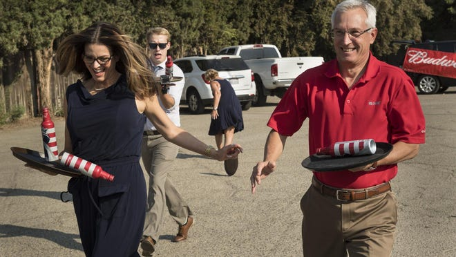 Realtors Olga Robles, left, Vernon Spence, Barbara Summers and Ed Evans practice for competing in Manny's Bud Dash for Cash during the annual Waiters Race in Visalia on Thursday, September 8, 2016.