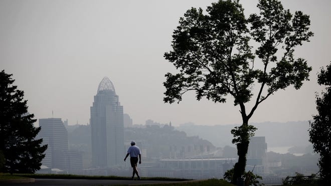 Charles Bucklew of Ludlow walks in Devou Park in Covington, against the backdrop of a hazy Downtown Cincinnati skyline in 2011. The Ohio Valley region was under a smog alert that day because of high heat, humidity and calm winds.