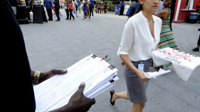 A petitioner, left, asks voters to sign petitions during lunch at Campus Martius Park in 2017. A group seeking to repeal Michigan's prevailing wage construction law submitted enough valid signatures to advance its measure to the state Legislature this year after failing to do so in 2015, according to elections staff.