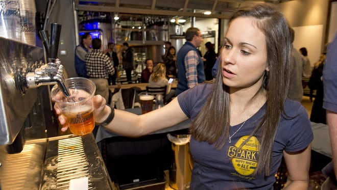 Hundreds turned out for the Braxton Brewing Company's grand opening in Covington Friday night. Annette Cardenas of Columbia Tusculum keeps the taps flowing.