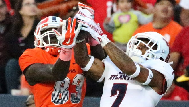 UTEP wide reciever Tyler Batson, 83, left, fights for the football along with Florida Atlantic's Cre'von LeBlanc, 7, right, during a long pass with 29 seconds left in the first half Saturday in the Sun Bowl. Neither player came up with the catch as it was ruled incomplete.