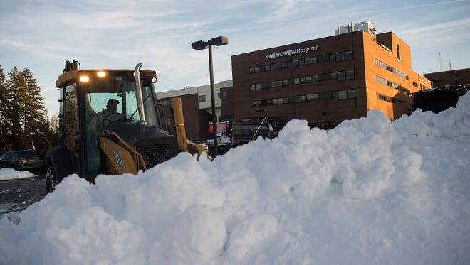 A driver clears snow in front of Hanover Hospital on Jan. 25, 2016.