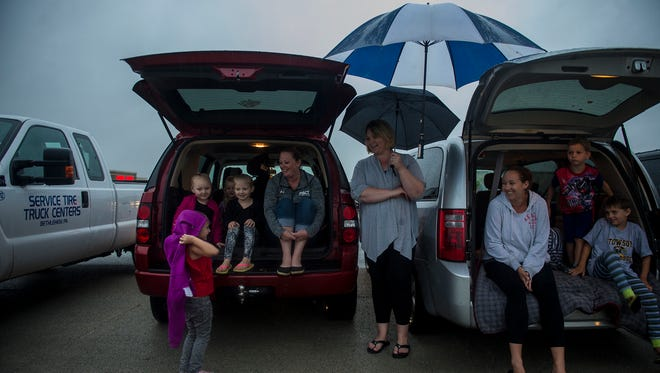 Friends Megan Prajzner, left, Lindsay McKenzie, center, and Kristen Poisal, right, all of Hanover, wait with their kids for the fireworks to begin Monday at the Wilson Avenue site.