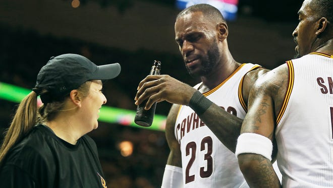 Cleveland Cavaliers forward LeBron James ends up with a beer bottle in his hand after running into a floor server in Game 1.