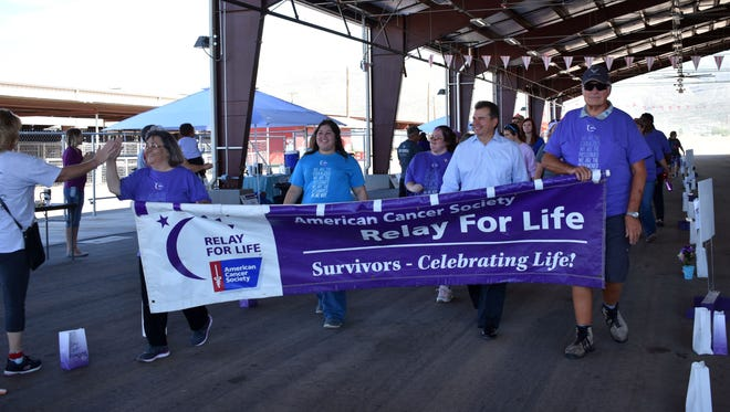 Sue Baker of the Cancer Resource Center receives a high-five as the survivors finish their opening lap during Alamogordo's Relay for Life on Saturday afternoon.