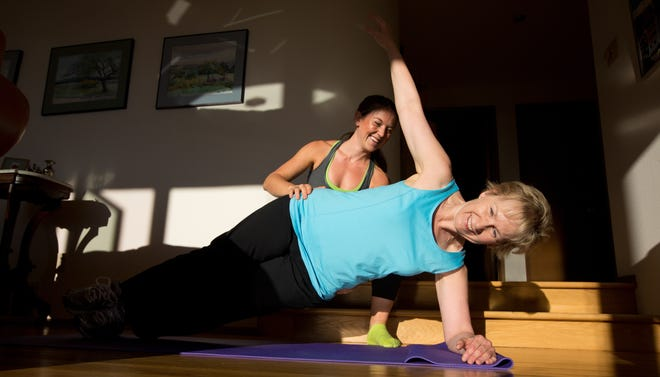 Anne McTiernan, a cancer researcher, works out at her Seattle home with her personal trainer, Whitney Mack.